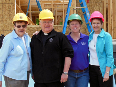 The Wake Up the World Local Leader Team: Sr. Janet Marie Peterworth, OSU; Fr. John Schork, CP; Sr. Teresa Gunter, OSB; and Sr. Nancy Gerth, SCN, in front of the construction site of the Pope Francis House.