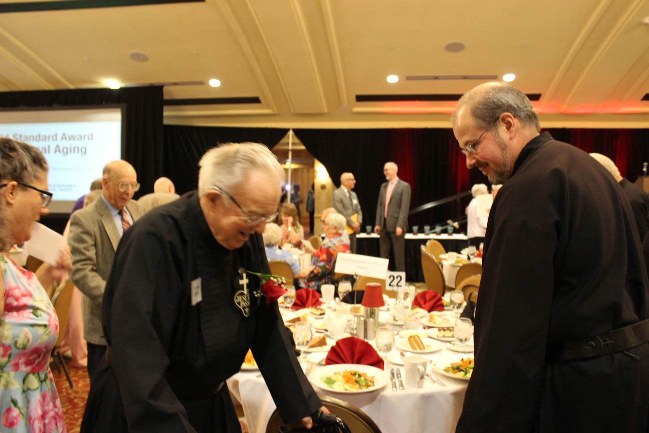 Br. Kurt Wernert, CP, assists Fr. Simon as he takes his seat.