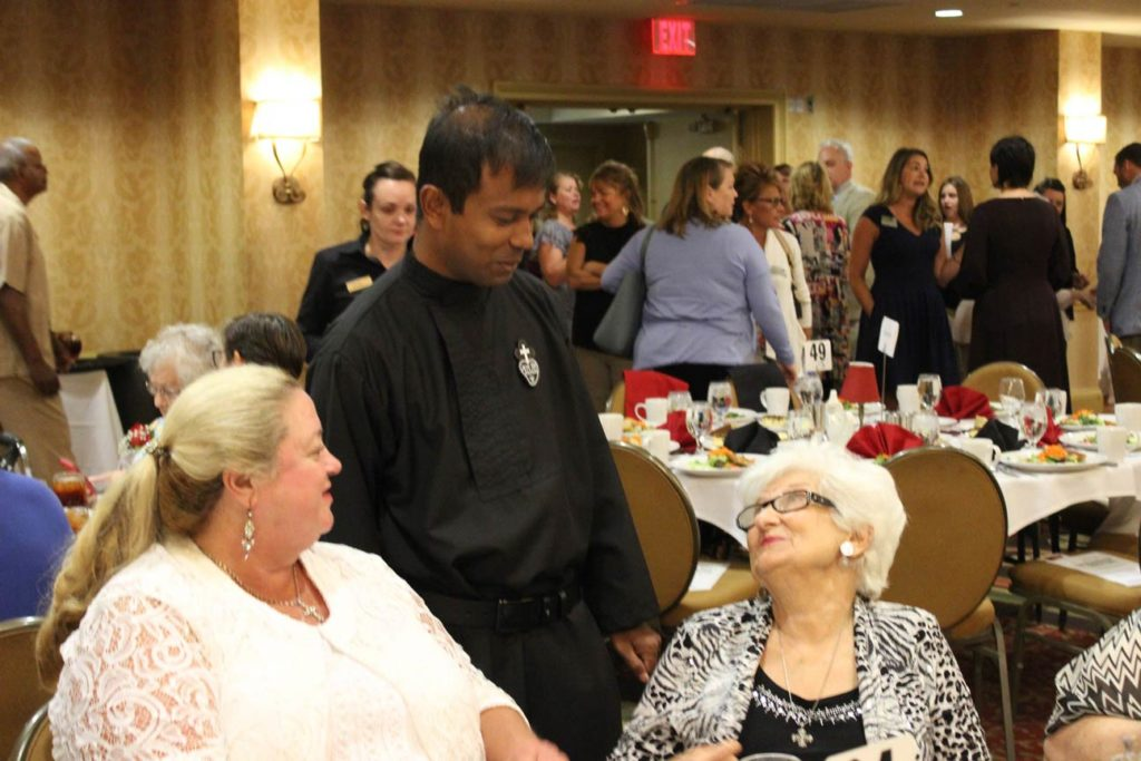 Fr. Febin Barose, CP, chats with Mary Anne Kaelin and Dee Dee Lockhart.