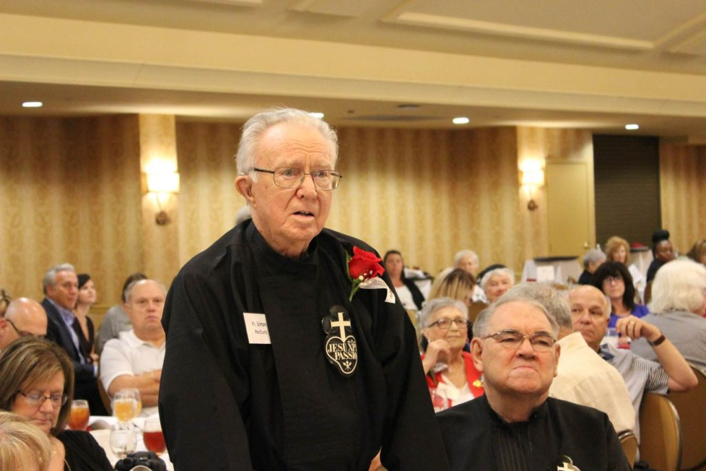 Fr. Simon stands to receive his award, with Br. John Monzyk, local superior of Sacred Heart Monastery, next to him.
