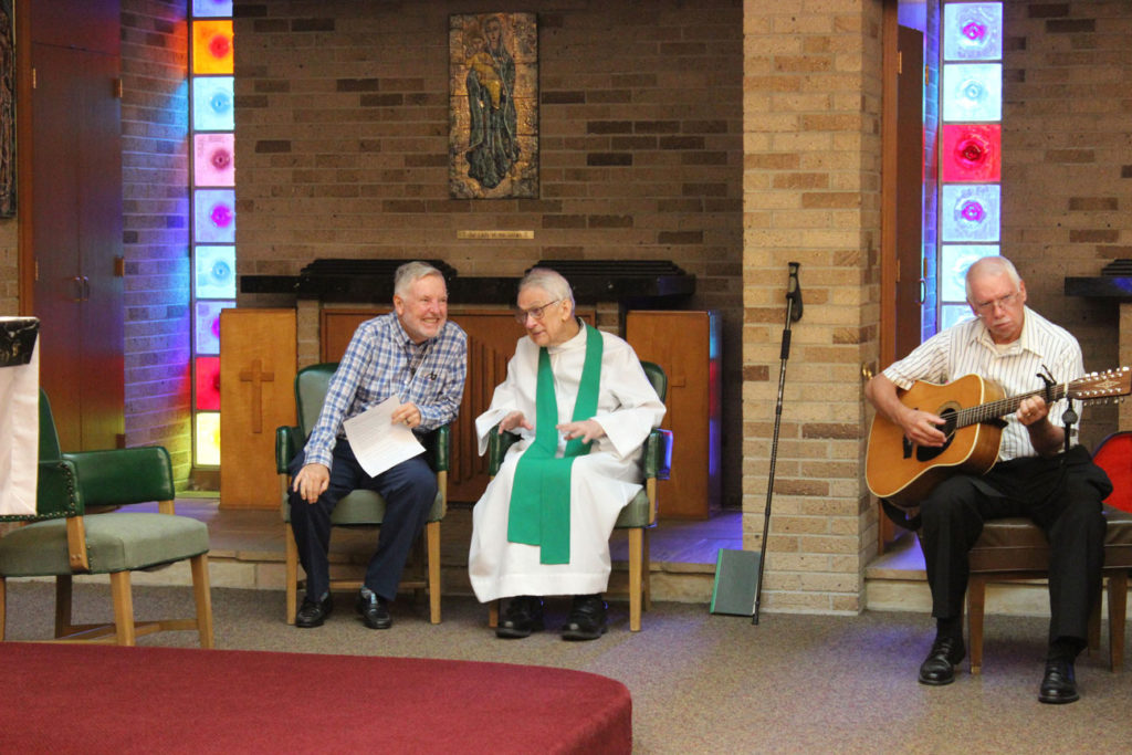 Bob Durr and Fr. Peter Berendt, CP, chat before Mass. Ray Williams preps the guitar.